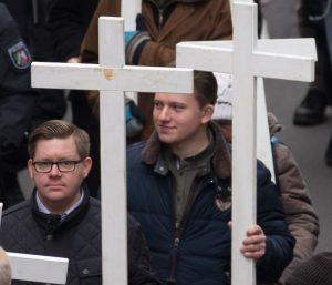 Alexander Leschik trägt ein weißes Holzkreuz